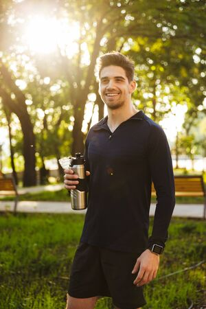 Image of a handsome smiling young sports fitness man standing in green park nature holding bottle with water.
