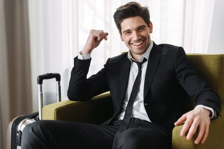 Photo of happy european businessman wearing black suit sitting on armchair with suitcase in hotel apartment