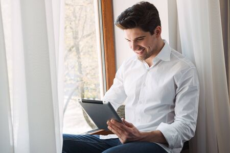 Photo of smiling brunette man wearing white shirt making video call on tablet computer while sitting at window in living room