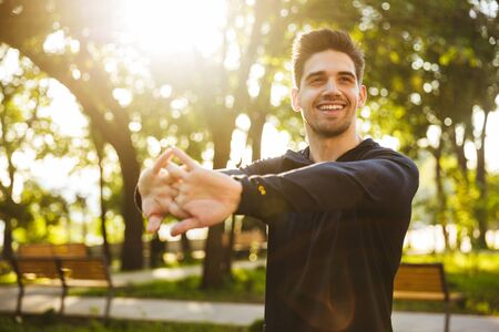 Image of a handsome smiling young sports fitness man standing in green park nature make stretching exercises for arms. Stock Photo