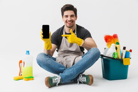 Image of a happy excited young houseman househusband with cleansers on floor isolated over white wall background showing display of mobile phone.