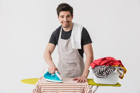 Handsome brunette houseman wearing apron standing isolated over white background, ironing clothes on a board Stockfoto