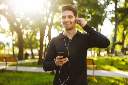 Portrait of handsome athletic man dressed in sportswear listening to music with earphones and smartphone while doing workout in sunny green park Stockfoto