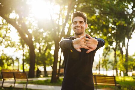 Image of a handsome cheerful young sports fitness man standing in green park nature make stretching exercises for arms. Stock Photo