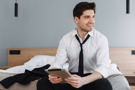 Photo of handsome smiling businessman wearing formal clothes using tablet computer while sitting on bed in hotel apartment Фото со стока