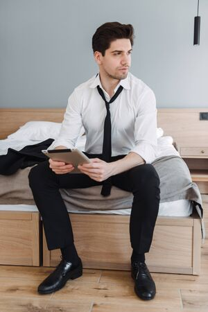 Photo of handsome brooding businessman wearing formal clothes using tablet computer while sitting on bed in hotel apartment