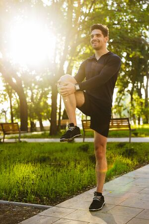 Image of a handsome cheerful young sports fitness man standing in green park nature make stretching exercises for legs.