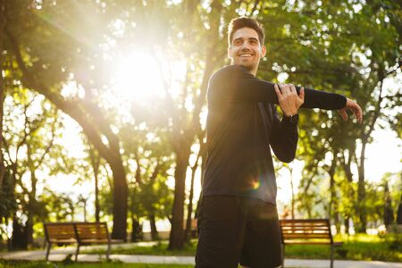 Image of a handsome happy pleased young sports fitness man standing in green park nature make stretching exercises for arms. Stock Photo