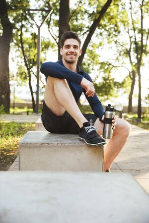 Portrait of young athletic man dressed in sportswear sitting on bench and holding water bottle while doing workout in sunny green park