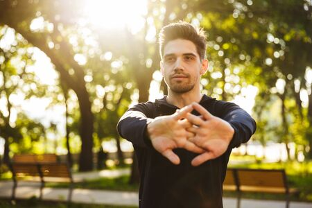 Image of a serious young sports fitness man standing in green park nature make stretching exercises for arms. Stock Photo