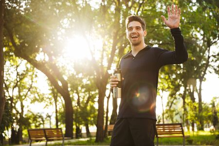 Image of a handsome cheerful young sports fitness man standing in green park nature holding bottle with water waving to friends. Stock Photo