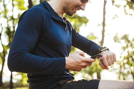 Portrait of satisfied athletic man dressed in sportswear sitting on bench with cellphone and looking at wristwatch while doing workout in sunny green park