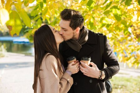 Beautiful young couple in love spending time together at the park in autumn, embracing, holding takeaway coffee cups