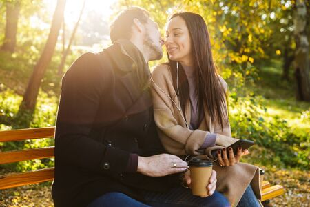 Cheerful young couple spending fun time at the park in autumn, sitting on a bench, listening to music with earphones