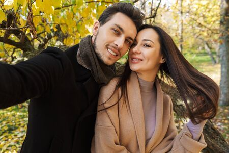 Beautiful young couple in love spending time together at the park in autumn, taking a selfie, hugging Stock Photo
