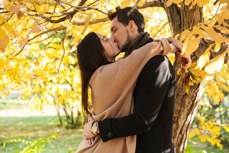 Cheerful young couple spending fun time at the park in autumn, embracing, kissing