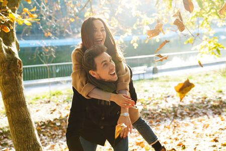 Cheerful young couple spending fun time at the park in autumn, piggyback ride