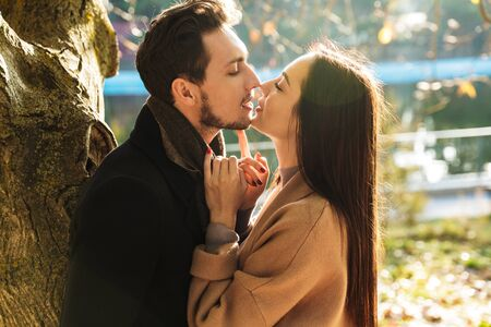 Image of a happy young beautiful loving couple posing walking outdoors in park nature kissing. Standard-Bild - 127733231