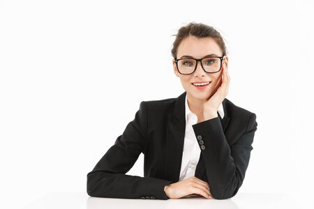 Photo of smiling female worker businesswoman dressed in formal wear looking at camera while working and sitting at desk in office 版權商用圖片