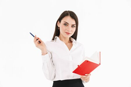 Photo of successful female worker businesswoman dressed in formal wear holding day planner while working in office isolated over white