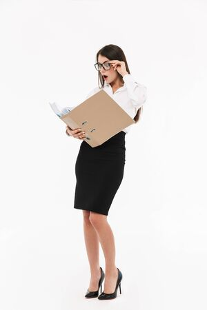 Photo of caucasian female worker businesswoman dressed in formal wear holding bookbinder with documents while working in office 스톡 콘텐츠