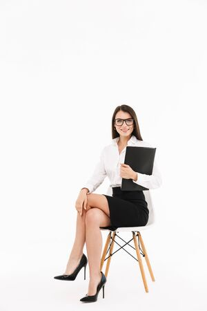 Photo of smiling female worker businesswoman dressed in formal wear holding bookbinder with documents while sitting in office chair isolated over white background 스톡 콘텐츠