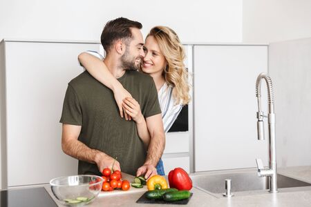Image of a happy young loving couple posing at the kitchen at home cooking have a breakfast hugging. Imagens