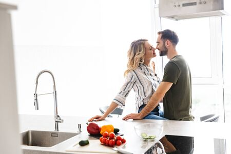 Photo of a tender young romantic loving couple indoors at the kitchen cooking vegetable salad have a breakfast hugging kissing.