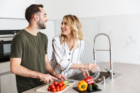 Image of a happy young loving couple posing at the kitchen at home cooking have a breakfast. Archivio Fotografico