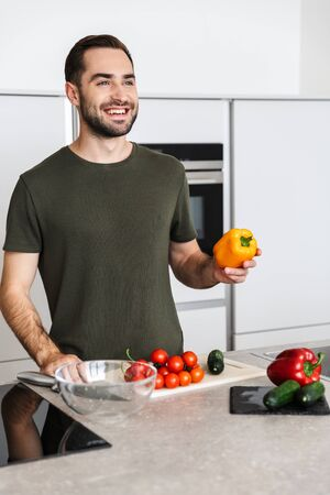 Photo of a smiling young bearded man indoors at the kitchen cooking vegetable salad have a breakfast.