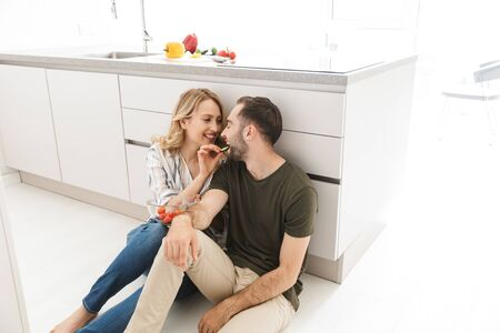 Photo of a smiling cute young loving couple indoors at the kitchen eat vegetable salad have a breakfast sitting on floor. Imagens