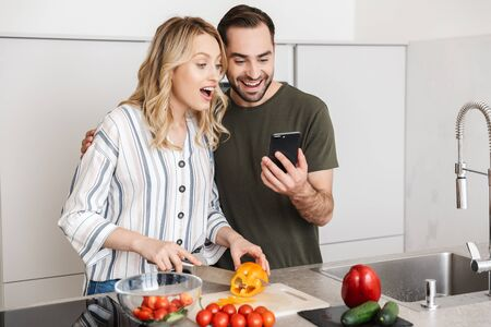 Image of a happy young loving couple posing at the kitchen at home cooking have a breakfast using mobile phone.