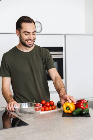 Image of a happy young handsome man cooking at the kitchen at home have a breakfast.