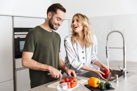 Image of a happy young loving couple posing at the kitchen at home cooking have a breakfast laughing.
