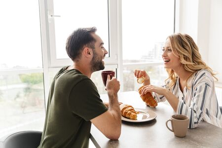 Photo of a laughing young loving couple indoors at the kitchen have a breakfast eat croissant and corn flakes with milk.