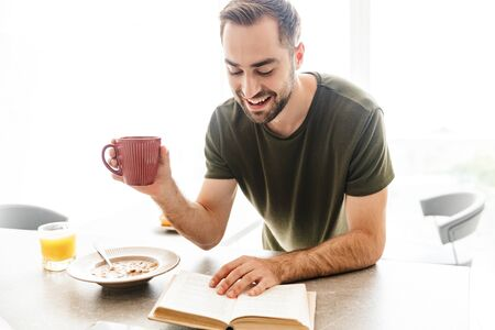 Photo of a cheerful young bearded man indoors at the kitchen have a breakfast eat corn flakes with milk reading book drinking coffee. Banco de Imagens