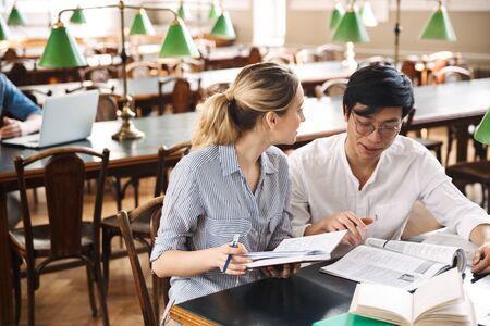 Smart cheerful teenagers studying at the library together, reading books Stockfoto