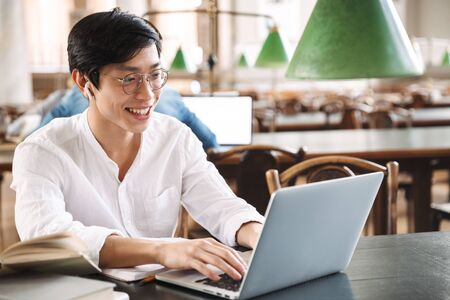 Confident asian man student wearing earphones studying at the library with laptop and books