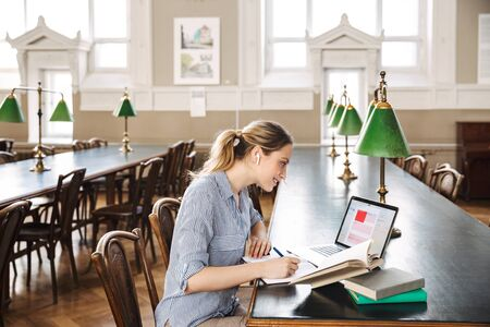 Attractive blonde girl student studying at the library with laptop computer