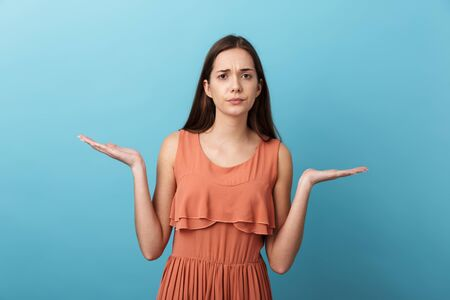 Cute confused lovely young girl standing isolated over blue background Stock Photo