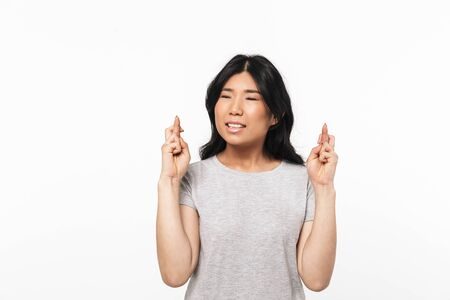 Image of asian nervous beautiful young woman posing isolated over white wall background make hopeful gesture.