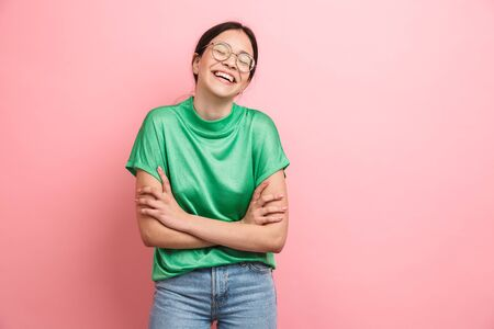 Photo of happy young girl wearing round eyeglasses laughing at camera while standing with arms crossed