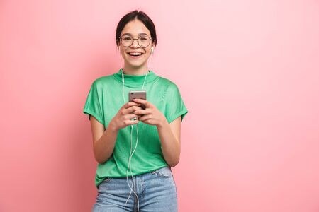 Photo of smiling young girl wearing round eyeglasses using earphones while holding smartphone