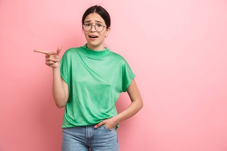 Photo of young teenager girl wearing round eyeglasses smiling and pointing finger aside