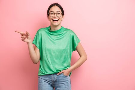 Photo of joyful young girl wearing round eyeglasses smiling and pointing finger aside