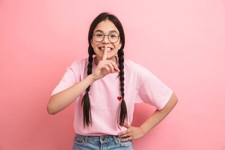 Image of european teen girl with two braids wearing eyeglasses holding index finger on lips and asking to be quiet