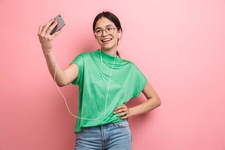 Photo of cute young girl wearing round eyeglasses taking selfie on mobile phone while using earphones isolated over pink background