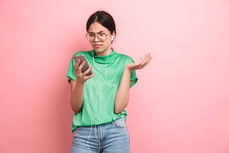 Photo of puzzled young girl wearing round eyeglasses using earphones while holding smartphone isolated over pink background Banco de Imagens