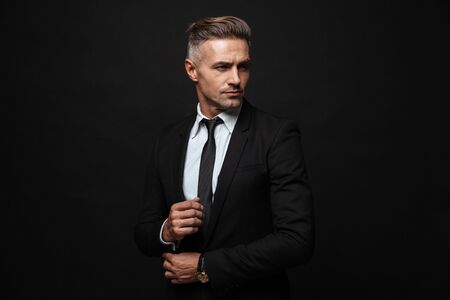 Portrait of european handsome businessman dressed in formal suit posing and looking aside isolated over black wall Standard-Bild