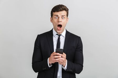 Image of shocked yong businessman in formal suit typing on cellphone and looking at camera with open mouth isolated over gray background